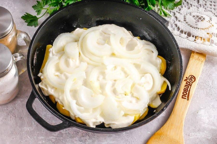 Очистите картофель и лук от кожуры, промойте в воде. Нарежьте картофель кружочками или ломтиками, лук — полукольцами. Смажьте форму для запекания растительным маслом и выложите в нее картофельную нарезку. Посолите. Смажьте картофель сметаной любой жирности или майонезом. Можно залить даже кефиром, если вы любите менее калорийные варианты. Сверху выложите луковую нарезку.