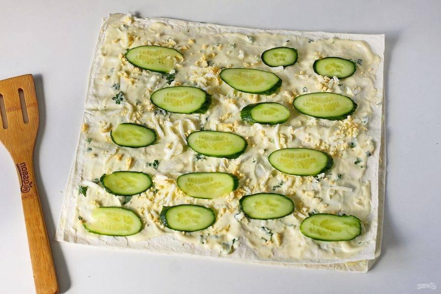 Накройте начинку вторым лавашом и повторите слои еще раз в том же порядке: соус, яйца, огурец.