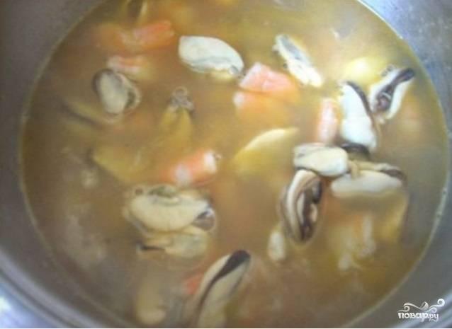 Затем добавьте картофель. Готовьте 5 минут, помешивая. Влейте воду с морепродуктами и доведите до кипения.