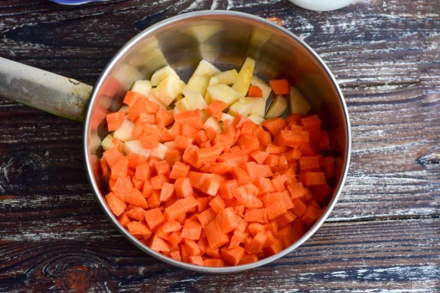 Выложите яблоки и морковь в ковш или кастрюлю.