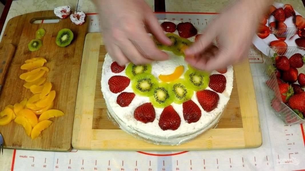 Далее накладываю верхний корж, также обильно пропитанный жидкостью из компота, и украшаю сначала сливками по кругу и сверху хорошим слоем и фруктами: клубникой, киви и остатками персиков.