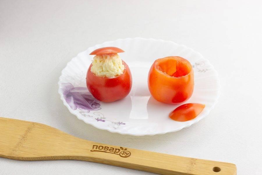 У помидоров срежьте небольшую макушку, которая послужит нам шапочкой. Мякоть аккуратно удалите чайной ложкой. Её можно использовать для зажарки или подливы. Начините помидор сырной массой с небольшой горкой для головы.