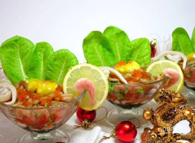 Далее выкладываем рыбу, тертые яйца, креветки и кальмары. Верхушку украшаем красной икрой, яичными желтками и дольками лимона. Приятного аппетита!