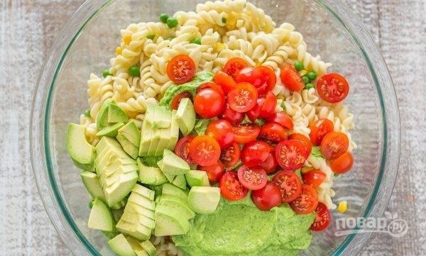 3.  В блюдо с макаронами нарежьте помидоры и оставшееся авокадо. Перемешайте салат и подавайте на стол.