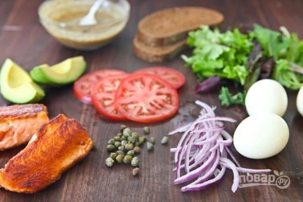 1.Отварите куриное яйцо и разрежьте его на 4 ломтика. Вымойте томаты и разрежьте их тонкими кольцами, очистите луковицу и нашинкуйте мелкими полукольцами. Очистите авокадо от кожуры, удалите косточку и разрежьте ломтиками, вымойте зелень. Обжарьте лосось на раскаленной сковороде-гриль с 3 столовыми ложками оливкового масла.