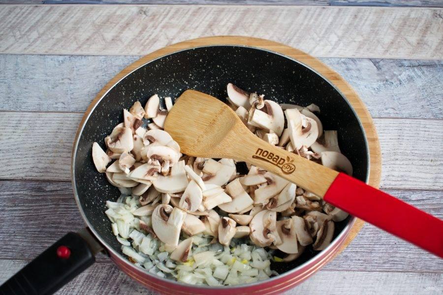 На сковороде разогрейте оливковое масло. Лук измельчите, пассеруйте до прозрачности. Добавьте мелко нарезанные грибы, перемешайте, готовьте до выпаривания жидкости.