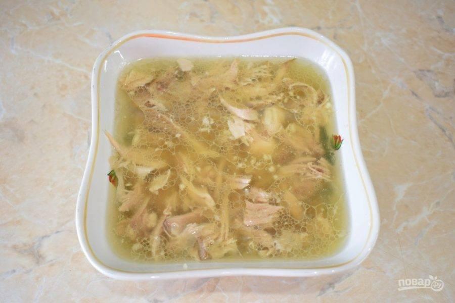 После длительной варки мясо извлеките из чаши, удалите кости и разложите его по тарелкам для холодца. Бульон процедите и разлейте по тарелкам. Добавьте в каждую тарелку немного чеснока.