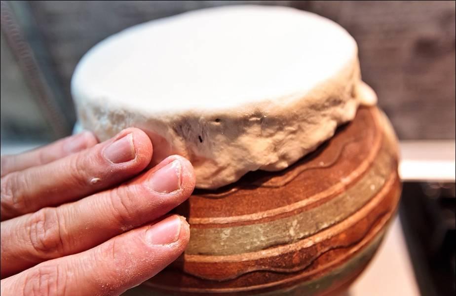 Раскатываем тесто в блинчик и накрываем им горшок, плотно прижав тесто к горлышку.