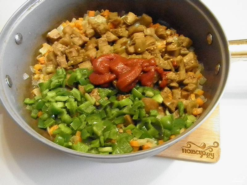 К полуготовым луку и моркови добавьте баклажаны, сладкий перец и томатную пасту. Протушите 10-15 минут.