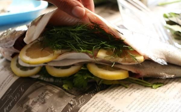 2. Зелень разделите на 4 равные части и заполните брюшко каждой рыбки. Лимон нарежьте тонкими ломтиками и также поместите внутрь. Если есть возможность, используйте в рецепт приготовления форели на мангале и лимон, и лайм.