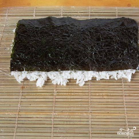 2. Накрыть лист нори вместе с рисом циновкой и перевернуть на другую сторону.