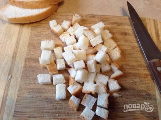 В первую очередь приготовим сухарики к супу. Нарезаем ломтики белого хлеба на небольшие кубики.