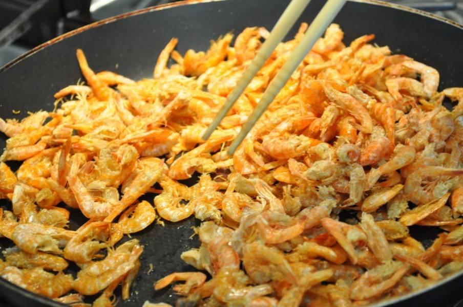 Налейте масло растительное в сковороду, разогрейте его. Затем добавьте креветки, помешивая, готовьте минуты 3.