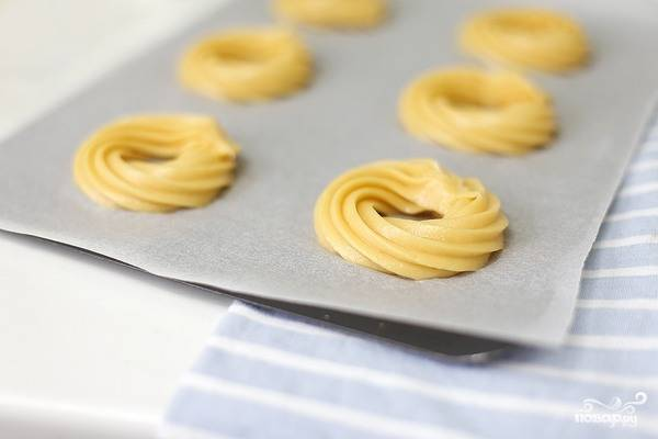 Смешайте все ингредиенты для теста в посуде с высокими стенками. Взбейте их до полной однородности. Переложите тесто в кулинарный мешочек и выдавите на пергамент для запекания колечками.