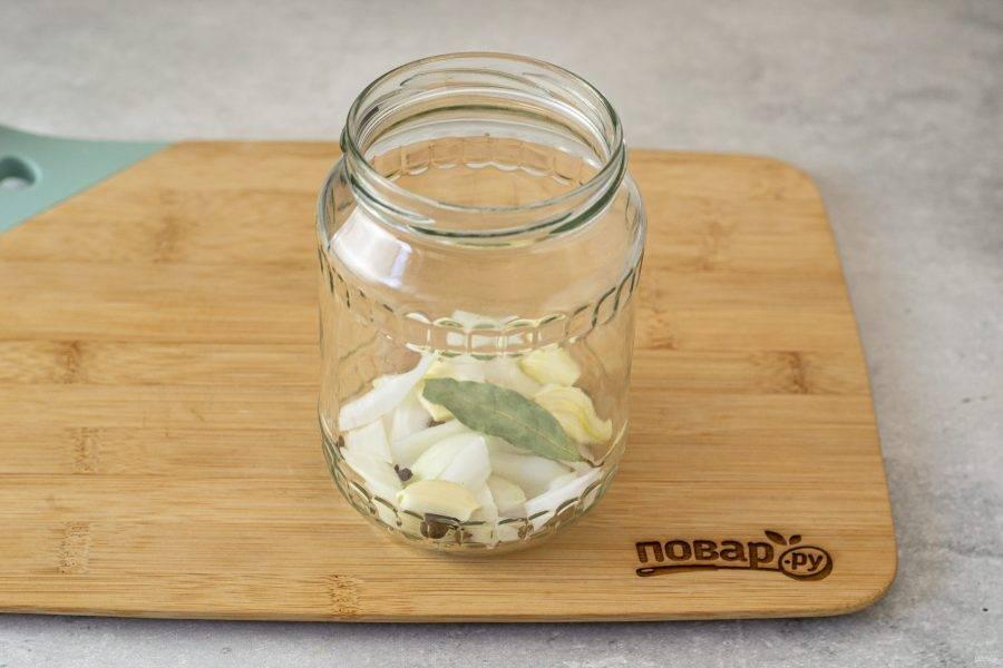 Выложите на дно чистой стерилизованной банки черный и душистый перец горошком, очищенный чеснок, гвоздику, лавровый лист и нарезанный ломтиками репчатый лук.