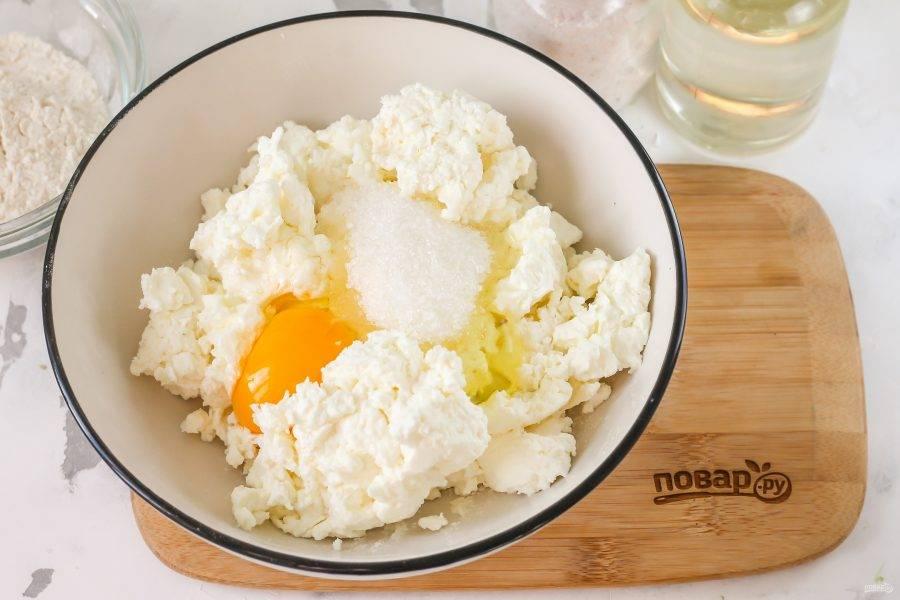 Творог выложите в глубокую емкость, вбейте туда же куриное яйцо, всыпьте соль и сахар. Тщательно все перемешайте.