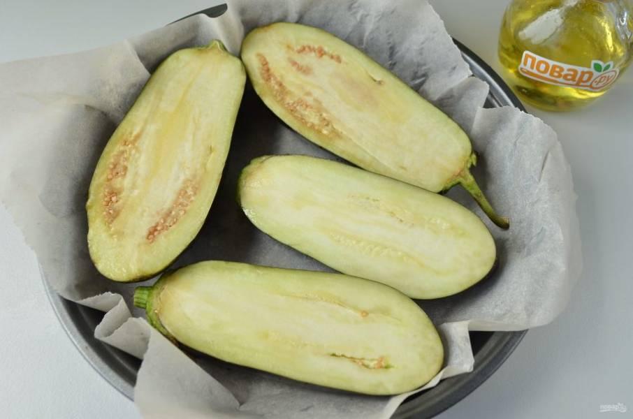 2. Вымойте баклажаны, порежьте их на половинки вдоль, каждую смажьте сверху растительным маслом и отправьте в горячую духовку на 20 минут (200 градусов).