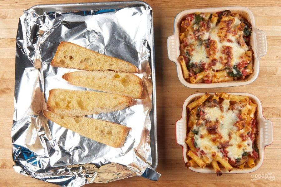 5. Далее переложите в форму для выпечки блюдо. Сверху натрите оба вида сыра. Запекайте ингредиенты при 180 градусах в течение 19 минут. А багет натрите чесноком и сливочным маслом, и запекайте его 7 минут.