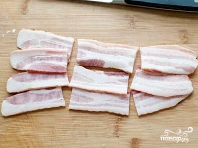 В это же время нарежьте бекон кусочками, а по краям промажьте их перцем с солью. Уберите его в отдельной чашке под полиэтиленом в холодильник на это же время.