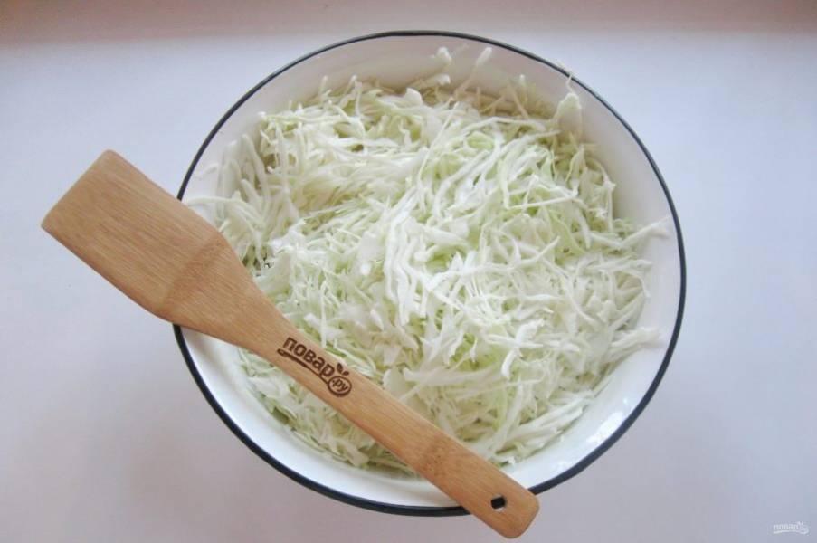 Удалите верхние листья кочана капусты. Нашинкуйте капусту тонкой соломкой и выложите в миску.
