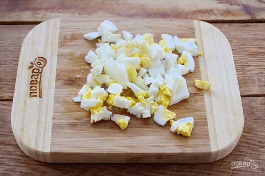 Отварные куриные яйца очистить и нарезать кубиком.
