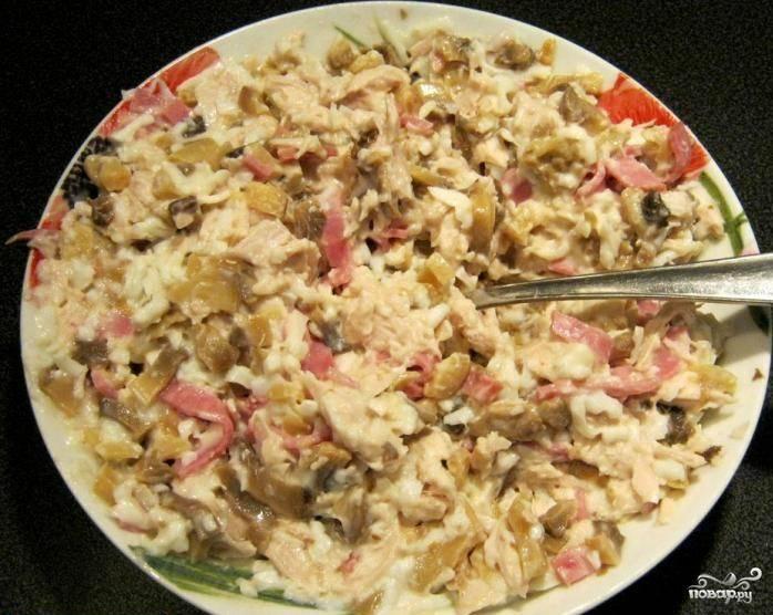 В отдельной тарелке смешиваем мясо курицы, ветчину, грибы и яичный белок. Добавляем майонез, перемешиваем.