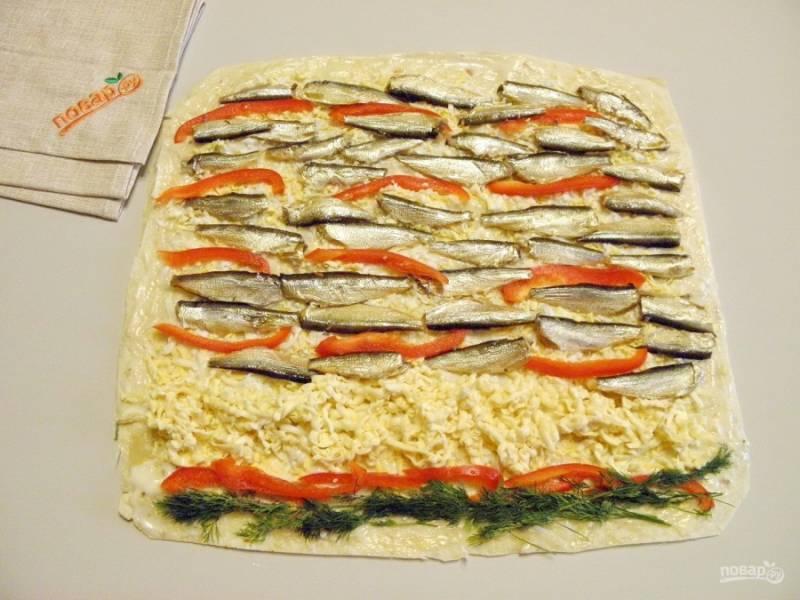 Отступите от края пару сантиметров и выложите тертый плавленный сыр, его не обязательно тереть, можно порезать брусочками. Порежьте тонкими соломками болгарский перец, распределите по лавашу. Разложите равномерно рыбу. Украсьте зеленью рулет.
