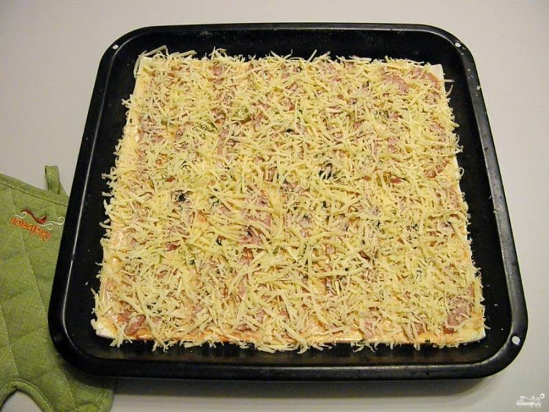 Щедро затрите пиццу слоем сыра. Чем больше сыра - тем вкуснее пицца.
