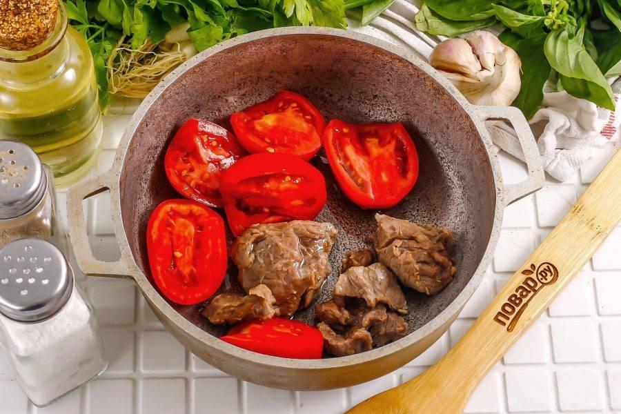 Промойте помидоры в воде и разрежьте их пополам. Срежьте зеленые сердцевинки. Лучше использовать небольшие плоды. Мясо нарежьте на части, прогрейте в казане растительное масло. Выложите в него половинки помидоров и нарезку мяса.
