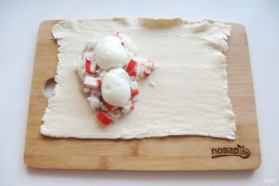Яйца сварите вкрутую, охладите и очистите. Одно яйцо разрежьте на две части вдоль и выложите на начинку.
