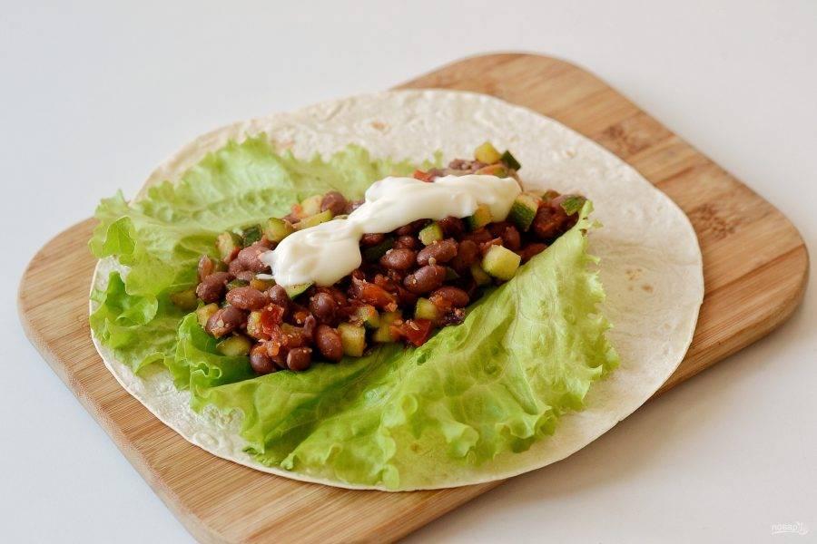 Выложите на лаваш салатный лист, сверху начинку из фасоли и овощей. Добавьте майонез. Сверните лаваш конвертиком.