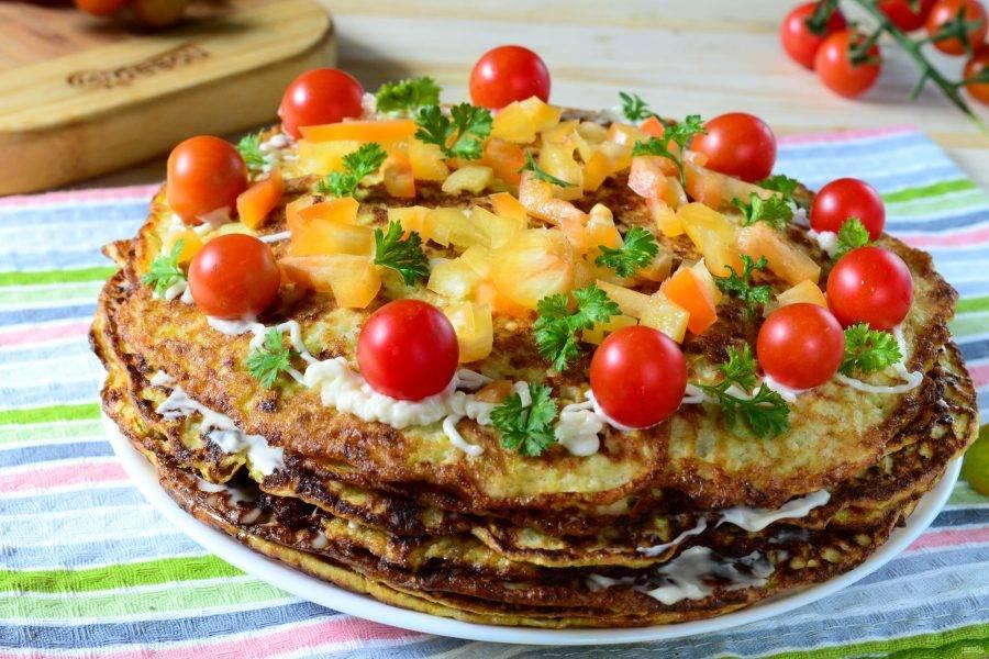 Таким способом соберите весь кабачковый торт. Сверху украсьте его целыми помидорами черри, измельченным сладким перцем и зеленью. Готовый торт отправьте в холодильник на 2 часа, чтобы он хорошо пропитался. Затем можно смело резать его на порционные куски и подавать к столу. Приятного аппетита!
