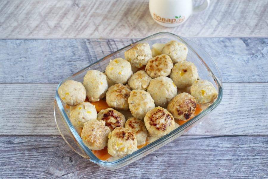 Сверху разместите фрикадельки. Полейте их горячими сливками, накройте форму фольгой. Поставьте запекаться в разогретую до 180 °С духовку на 25 минут. Снимите фольгу и запекайте еще 25 минут до готовности картофеля.
