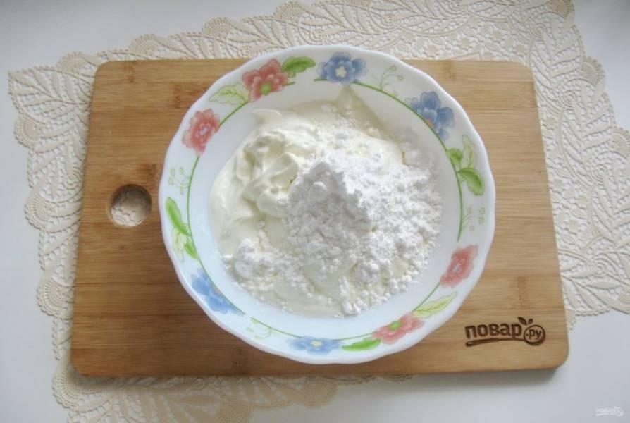 Приготовьте крем. В миску выложите сметану и добавьте сахарную пудру и ванильный сахар.