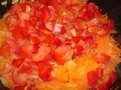 К луку добавляем измельченную морковь, помидоры и перец.