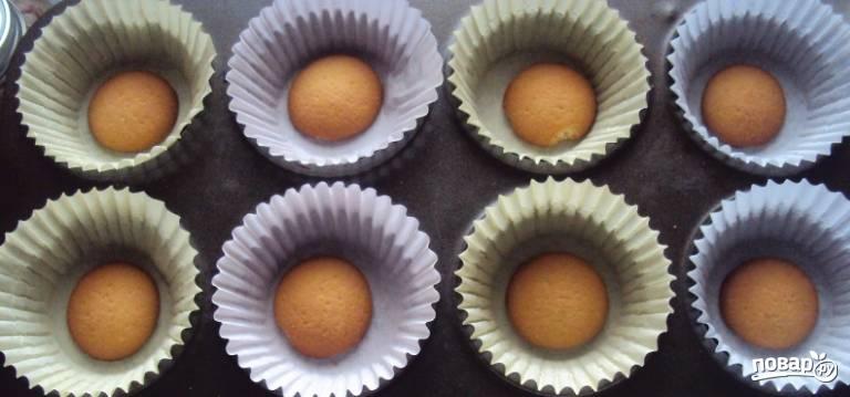 1. На дно формочек для кексов выкладываем печенье. Можно использовать бисквит, просто вырезать из него кружочки, или использовать готовые печеньки, как я.