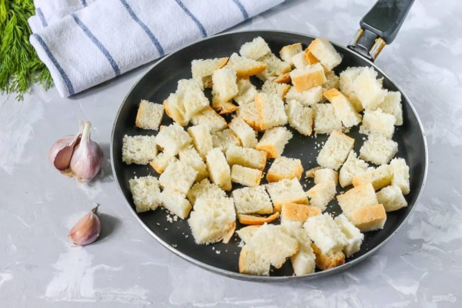 Прогрейте сковороду на умеренном нагреве и выложите в нее хлебную нарезку. Обжаривайте около 2-3 минут, перемешивая каждую минуту, чтобы сухарики равномерно прожарились со всех сторон. Выключите нагрев.