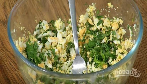 Отварите четыре яйца вкрутую, очистите и выложите их в миску. Разомните яйца вилкой или же натрите их на крупной терке. Нашинкуйте зелень, добавьте половину к яйцам. Посолите, поперчите и тщательно перемешайте все ингредиенты.