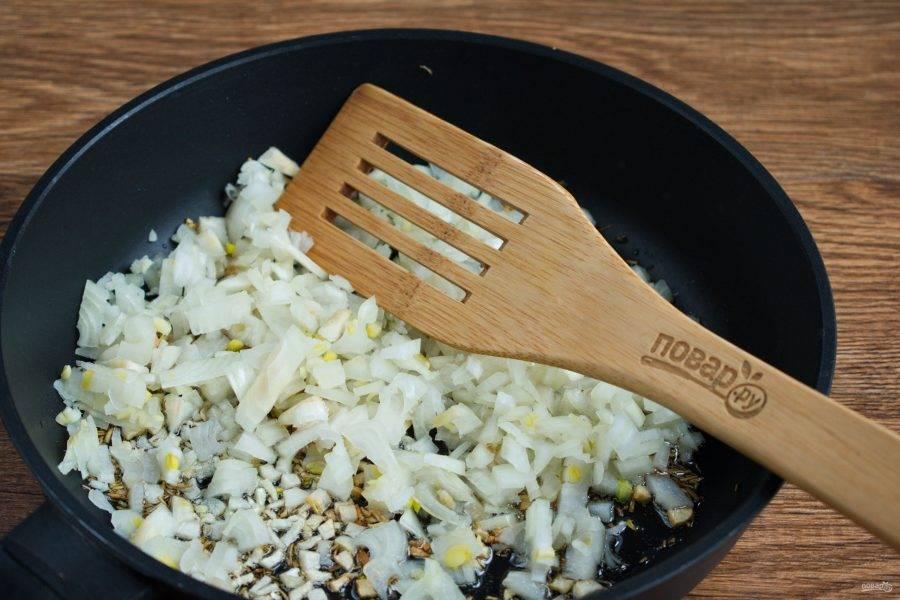 На сковороде разогрейте оливковое масло,  обжарьте зиру до появления запаха. Затем пассеруйте измельченный лук  до прозрачности. Добавьте измельченный чеснок, перемешайте.