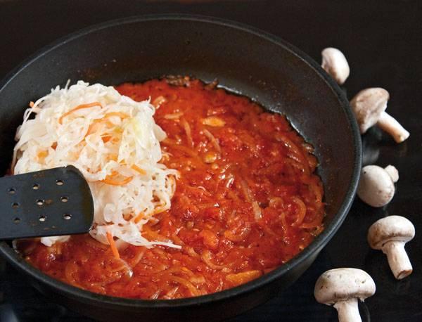 3. Протушив овощи минут 5, добавьте на сковороду кислую капусту и влейте пару ложек рассола. При желании поперчите немного.