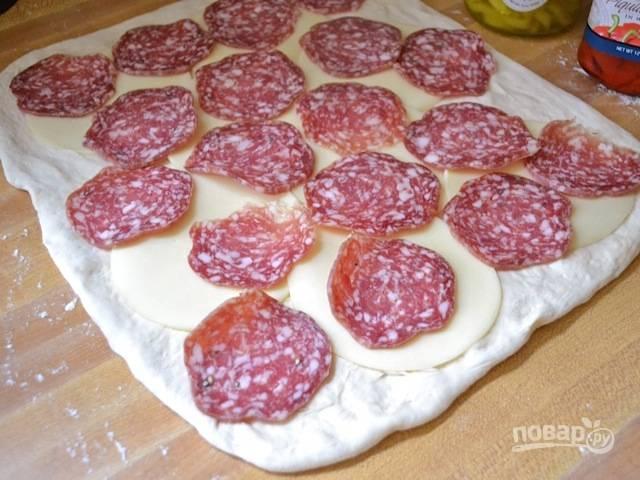 6.Выложите по всему пласту теста ломтики сыра и ломтики тонко нарезанной колбасы.