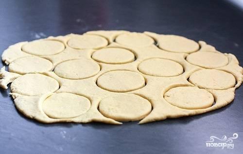 2. Когда тесто хорошо застыло, раскатайте его довольно тонко на рабочем столе. С помощью выемок или обыкновенного стакана вырежьте небольшие кружочки.