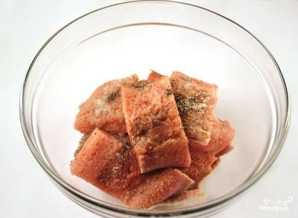 Теперь нам необходимо разрезать филе на порционные кусочки (обычно нарезаю на куски шириной 5-6 сантиметров). Посыпаем их солью, перцем, приправой для рыбы и поливаем лимонным соком. Хорошенько перемешиваем и оставляем на некоторое время промариноваться.