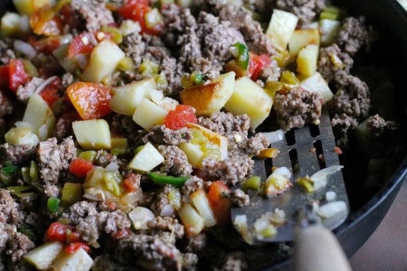 Добавьте мясной фарш и мелко порезанные помидоры. Хорошо перемешайте и обжаривайте минут 7.