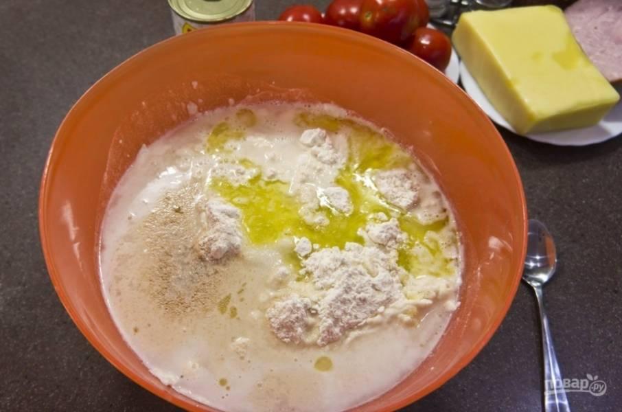 Сначала замесим тесто. Насыпаем в миску тесто, делаем углубление в горке, насыпаем туда дрожжи, наливаем оливковое масло, сыплем соль, наливаем 400 мл воды, сахар.