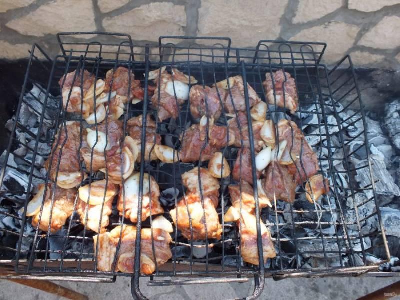 По истечении времени, мясо разложите на решетке или насадите на шампура. Обжаривайте на умеренно жарких углях в течение 20 минут.