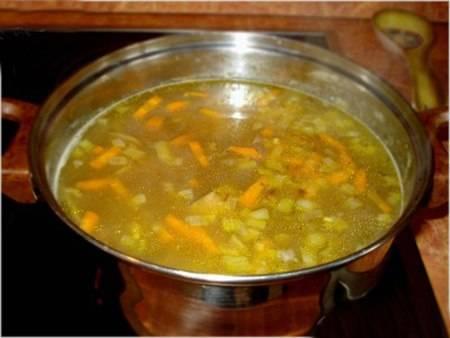 3. Чистим и моем овощи. Картошку нарезаем брусочками, отправляем к бульону с перловкой, а оставшуюся луковицу измельчаем и обжариваем на растительном масле с морковкой и чесноком. Все добавим, варим до готовности.