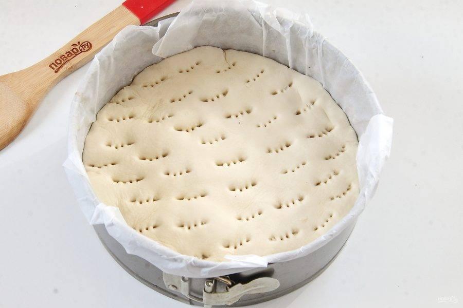 Слоеное тесто раскатайте чуть больше, чем размер формы. Вырежьте круг и накройте тестом колбаски, подгибая края внутрь. Сделайте проколы вилкой для выхода пара.