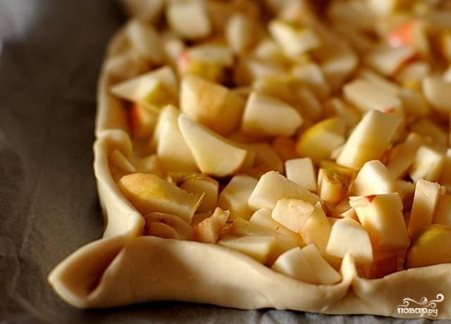 Сделайте начинку. Яблоки помойте и нарежьте на кубики. Мелко нарубите орехи. Выложите грецкие орехи и яблоки на тесто.