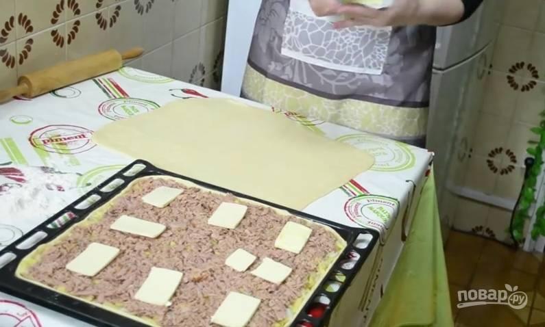 Холодное масло нарежьте на тонкие пластинки и положите на консервированного тунца, соблюдая равные промежутки между маслом.